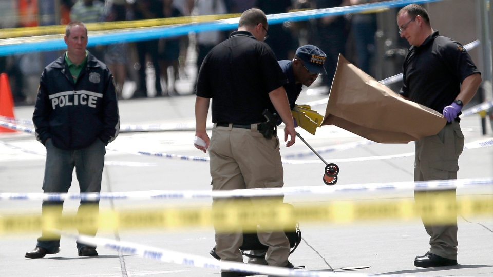 Officials collects evidence near the Empire State Building following a shooting, Friday, Aug. 24, 2012, in New York. (AP/Julio Cortez)