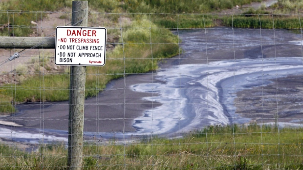 Tailings drain into a pond at the Syncrude oilsands mine facility near Fort McMurray, Alta. on July 9, 2008. (Jeff McIntosh / THE CANADIAN PRESS)