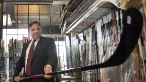 Coalition Avenir Quebec leader Francois Legault checks out a hockey stick during a visit to a sports store while campaigning Monday, August 27, 2012 in Boucherville, Que. THE CANADIAN PRESS/Ryan Remiorz