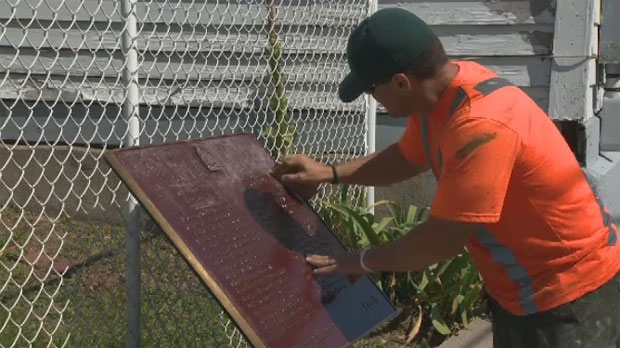 A city worker scrubs a commemorative plaque outside a Halifax church after someone scratched a racial slur into it.