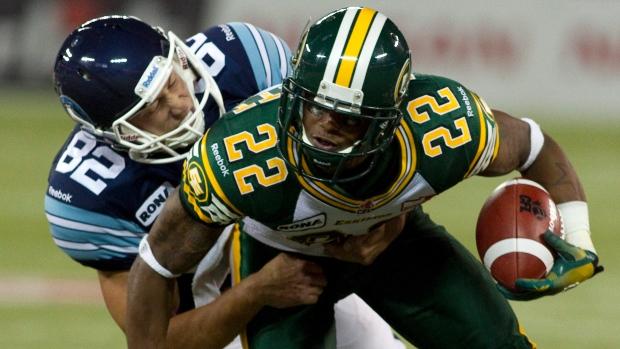 Edmonton Eskimos' Joe Burnett (right) is tackled by Toronto Argonauts' Chad Rempel
