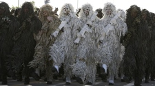 Iranian army troops march wearing ghillie suits on April 18, 2011.