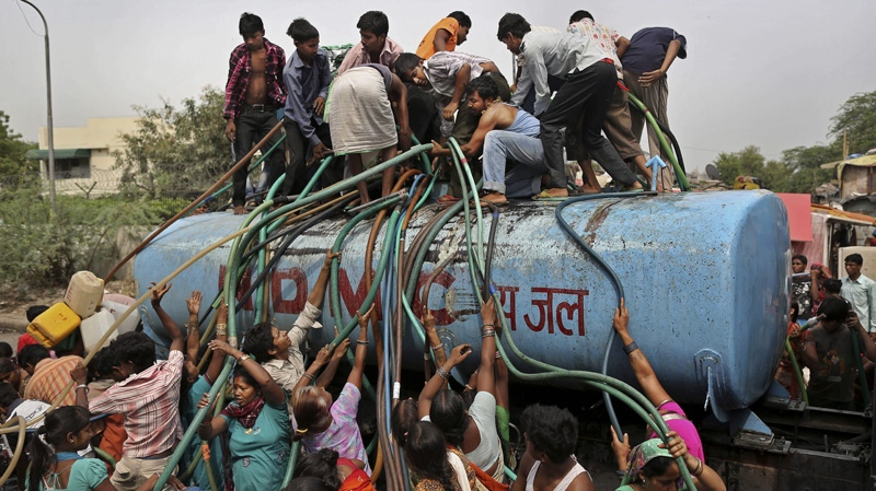 In this photo taken Friday, July 6, 2012, residents crowd around a government tanker delivering drinking water because of short supply in running water taps in New Delhi, India. (AP Photo/Kevin Frayer)