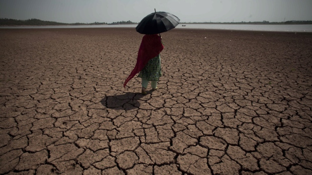 A Pakistani woman walks on a dry bank at Rawal dam in Islamabad, Pakistan on June 27, 2012.