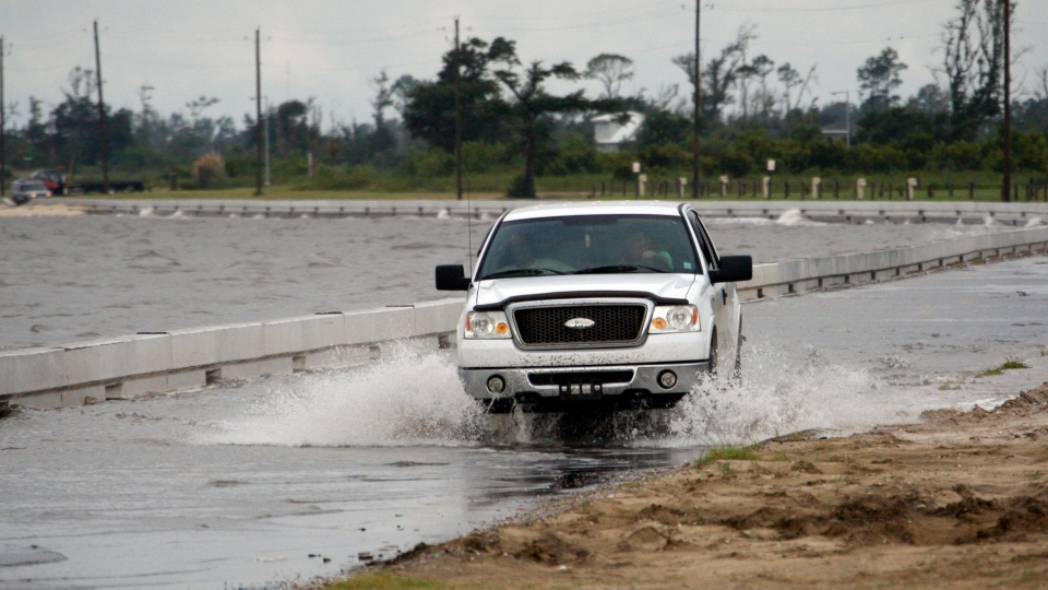 A truck runs though sea water along Beach Boulevard in Waveland, Miss., as Tropical Storm Isaac's winds begin to hit the Mississippi Gulf Coast, Tuesday, Aug. 28, 2012.  (AP / Rogelio V. Solis)