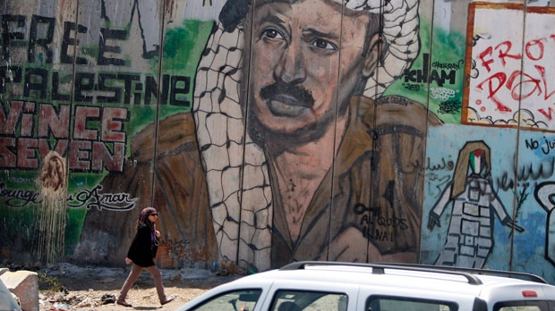 A Palestinian woman passes near a section of Israel's separation barrier depicting Yasser Arafat near the West Bank city of Ramallah on Wednesday, Aug. 8, 2012. (AP Photo/Majdi Mohammed)