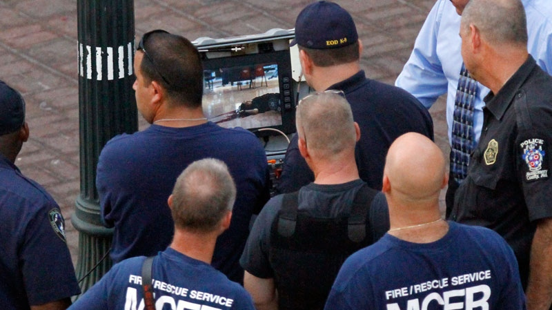 Authorities look at a screen that shows a live feed from a robot of James J. Lee, face up on the floor, inside the Discovery Channel network building where police shot and killed the gunman in Silver Spring, Md., Wednesday, Sept. 1, 2010. (AP / Jacquelyn Martin)