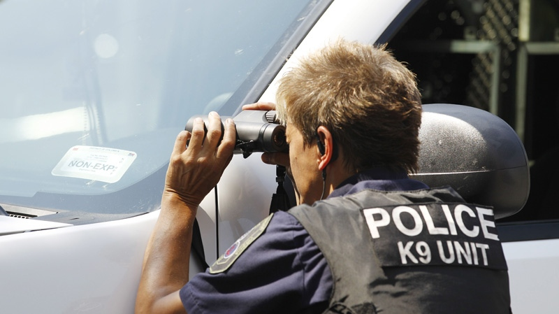 A police officer looks through binoculars on the street in front of the headquarters of the Discovery Channel networks building in Silver Spring, Md., Wednesday Sept. 1, 2010. (AP Photo / Jose Luis Magana)