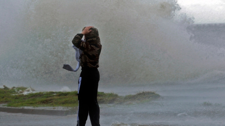 Matthew Nicaud braves the wind as waves crash over the seawall of Lake Pontchartrain at Canal Boulevard in New Orleans,Tuesday, Aug. 28, 2012 as Isaac approaches. (The Times-Picayune / John McCusker)