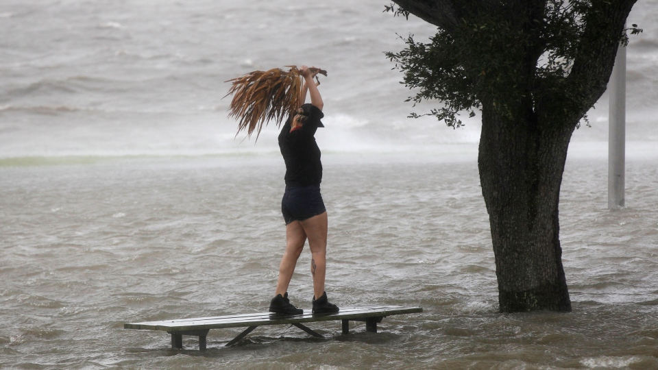A woman stands on a partially submerged picnic bench in the storm surge from Isaac, on Lakeshore Drive along Lake Pontchartrain, as the storm approaches landfall, in New Orleans, Tuesday, Aug. 28, 2012. (AP / Gerald Herbert)
