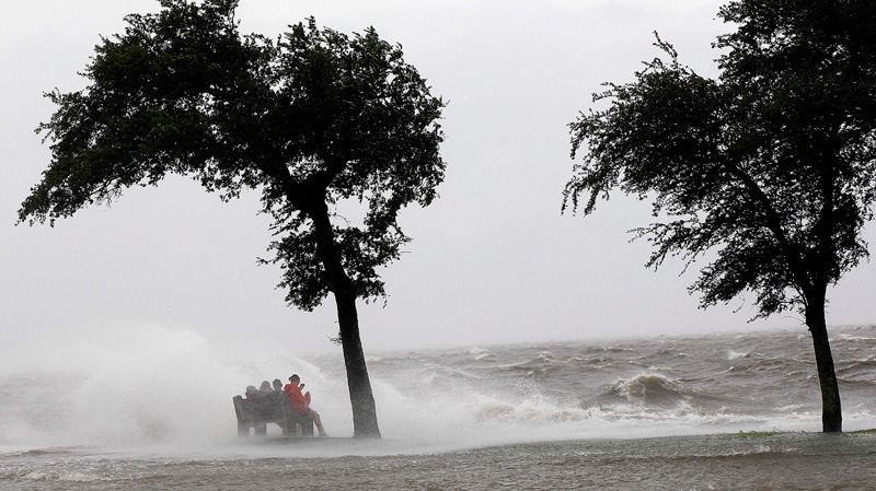 People sit on a bench along the seawall in the storm surge from Isaac, on Lakeshore Drive along Lake Pontchartrain, as the storm approaches landfall, in New Orleans on Tuesday, Aug. 28, 2012. (AP /Gerald Herbert)