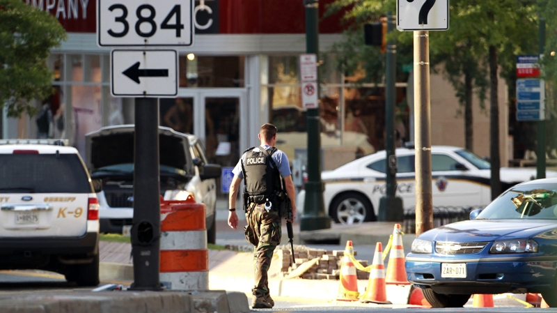 An armed police officer walks across the street from Discovery Channel network building in Silver Spring, Md., Wednesday, Sept. 1, 2010. (AP / Manuel Balce Ceneta)