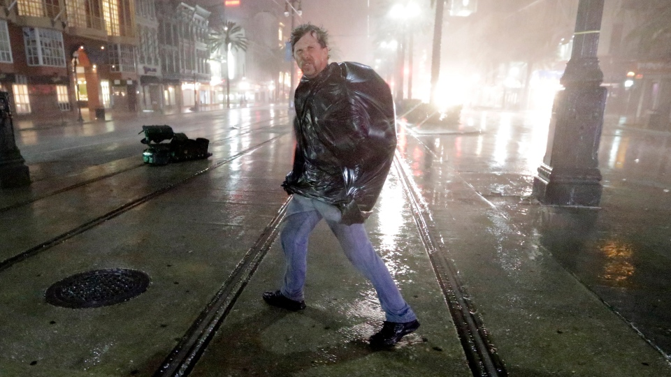 A man crosses Canal Street in the wind and rain as Hurricane Isaac strikes New Orleans, early Wednesday, Aug. 29, 2012. (AP / David J. Phillip)