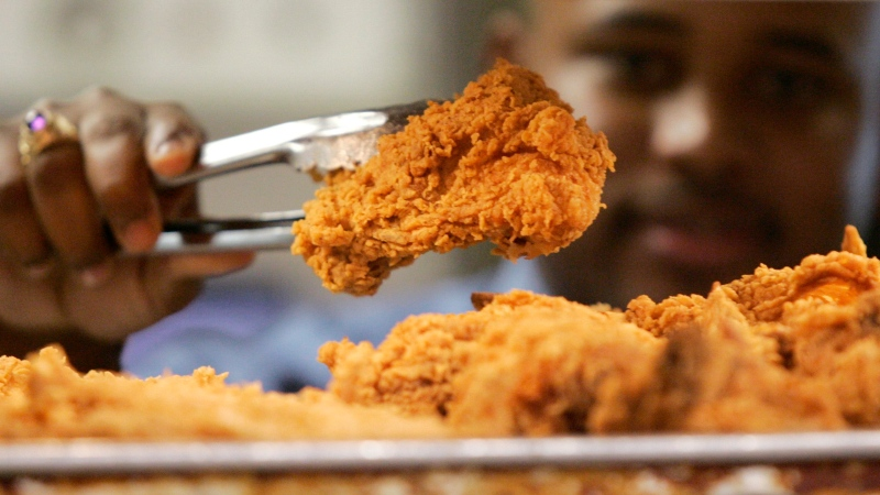 In this Monday, Oct. 30, 2006 file photo, a Kentucky Fried Chicken employee uses tongs to hold up an sample of the company's trans fat-free Extra Crispy fried chicken in New York. (AP / Kathy Willens, File)