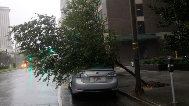 A tree lies on a car on Poydras St. downtown after Hurricane Isaac made landfall in New Orleans, Wednesday, Aug. 29, 2012.  (AP / Gerald Herbert)