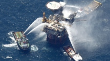 Boats are seen spraying water on an oil and gas platform that exploded in the Gulf of Mexico, off the coast of Louisiana., Thursday, Sept. 2, 2010. (AP / Gerald Herbert)