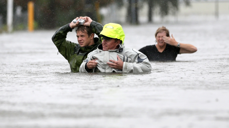 Chuck Cropp, centre, his son Piers, left, and wife Liz, right, wade through flood waters from Isaac Wednesday, Aug. 29, 2012, in New Orleans. (AP / David J. Phillip)