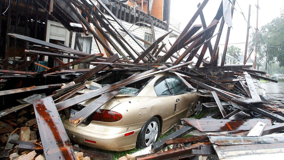 A house at the corner of N. Miro and Columbus Street collapsed during the height of Hurricane Isaac destroying three vehicles that were parked alongside it in New Orleans on Wednesday, Aug. 29, 2012. (AP /The Times-Picayune, David Grunfeld)