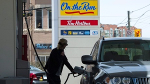 A woman pumps gas in Toronto in this file photo. (Nathan Denette / THE CANADIAN PRESS)