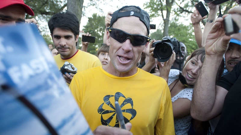 Lance Armstrong signs autographs following a run on Mont Royal Park in Montreal, Wednesday, August 29, 2012.  (THE CANADIAN PRESS/Graham Hughes)