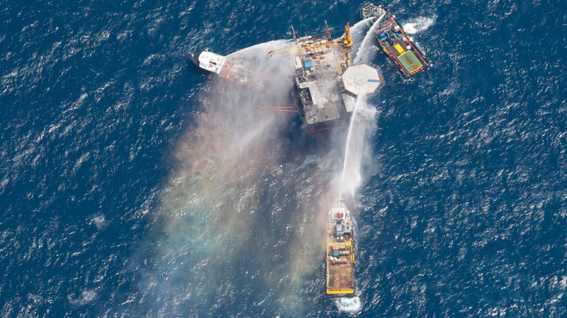 Boats are seen spraying water on an oil and gas platform that exploded in the Gulf of Mexico, off the coast of Louisiana, Thursday, Sept. 2, 2010. (AP / Gerald Herbert)