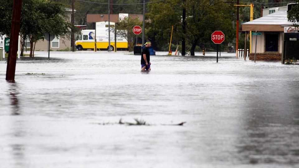 A man walks through a flooded street in Slidell, Louisiana on Thursday, Aug. 30, 2012. (AP / John Bazemore)