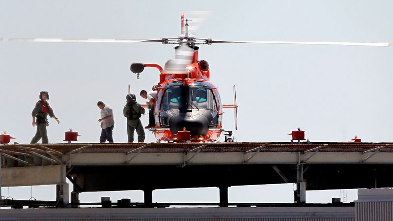 Two workers, who were rescued from an oil production platform that exploded 75 miles south of Vermillion Bay, step off of a U.S. Coast Guard helicopter on the roof of Terrebonne General Medical Center in Houma, La., Thursday, Sept. 2, 2010. (AP / Patrick Semansky)