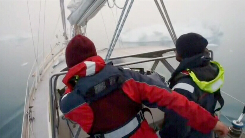 Two of the members who sailed the northernmost route through the Northwest Passage are seen in a boat from behind.