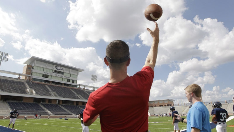 Football coach Jeff Fleener tosses a football to players during practice at the new $60 million football stadium at Allen High School Tuesday, Aug. 28, 2012 in Allen, Texas. (AP Photo/LM Otero)