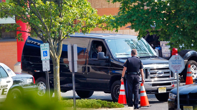 A van with the bodies of three people pulls away from a Pathmark supermarket on Route 9 in Old Bridge, N.J., Friday, Aug. 31, 2012. (AP / Rich Schultz)