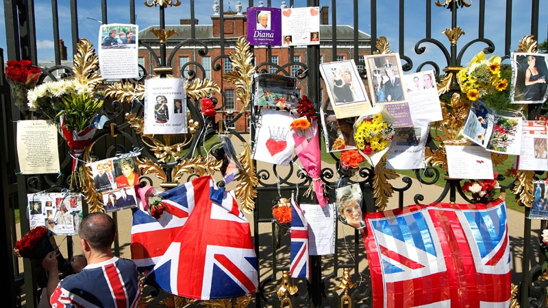 A man places a floral tribute for Britain's Princess Diana on the gate of Kensington Palace in London, on the 15th anniversary of her death, Friday, Aug. 31, 2012. (AP / Sang Tan)