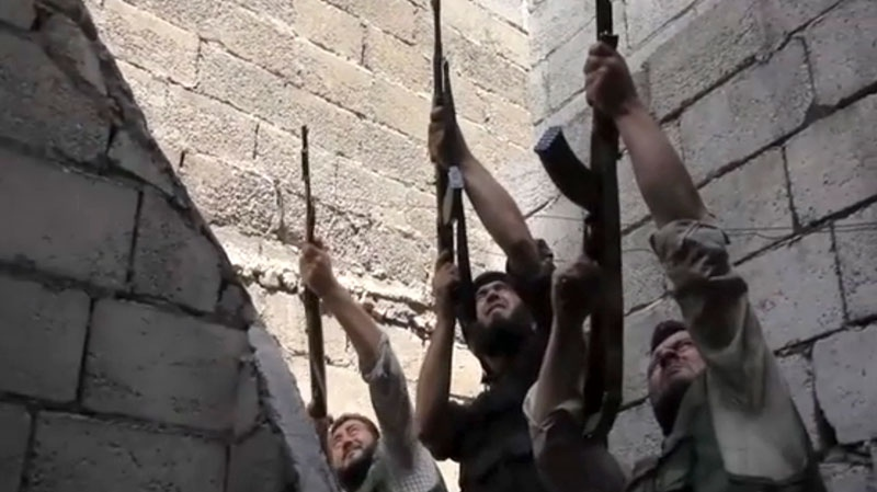 Free Syrian Army fighters raise their weapons during fighting with the Syrian Army in Aleppo, Syria, Saturday, Sept. 1, 2012. (AP)