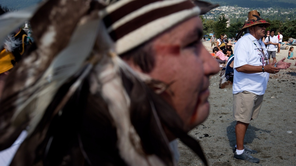 Squamish First Nation Chief Ian Campbell, left, listens as Chief Justin George, of the Tsleil-Waututh Nation, addresses the crowd before the First Nations paddled canoes on the waters of Burrard Inlet to the Kinder Morgan Burnaby Terminal for a ceremony to show opposition to the $5 billion expansion of the Trans Mountain pipeline, in West Vancouver, B.C., on Saturday, Sept. 1, 2012. (Darryl Dyck / THE CANADIAN PRESS)