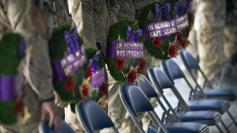 Canadians soldiers line up with wreaths to commemorate fallen Canadian soldiers during a next of kind memorial ceremony with family members at their base at Kandahar Airfield, Afghanistan, Saturday, Sept. 4, 2010. (AP Photo/Anja Niedringhaus)