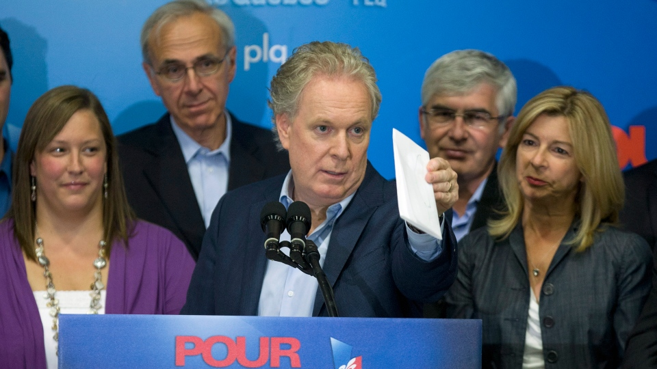 Quebec Liberal Party Leader Jean Charest, flanked by candidates, calls on voters at a rally in Quebec City on Sunday, September 2, 2012. (Jacques Boissinot / THE CANADIAN PRESS)