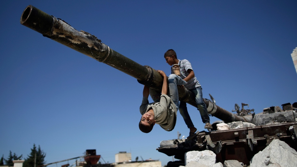 A boy looks back while he and another boy play on a Syrian military tank, destroyed during fighting with the Rebels, in the Syrian town of Azaz, on the outskirts of Aleppo, Sunday, Sept. 2, 2012. (AP / Muhammed Muheisen)