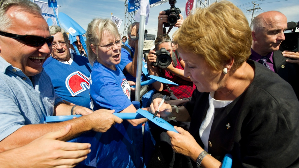 PQ leader Pauline Marois signs a plastic shovel at a sod turning rally for the city's new hockey rink Monday, Sept. 3, 2012 in Quebec City. (THE CANADIAN PRESS / Paul Chiasson)