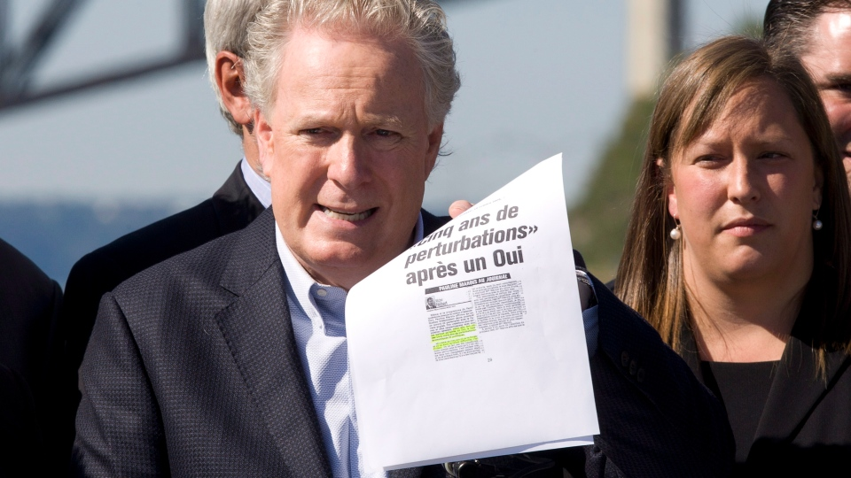 Quebec Liberal Party Leader Jean Charest holds an old newspaper article in which PQ Leader Pauline Marois was saying there would be five years of turmoil after a yes to sovereignty, during a news conference on the eve of a provincial election Monday, Sept. 3, 2012 in Quebec City. (Jacques Boissinot / THE CANADIAN PRESS)
