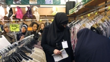 This April 4, 2010 file photo shows women in Islamic face-covering veils looking at clothes inside an exhibition hall during the 27th annual meeting of French Muslims, in Le Bourget, outside Paris. (AP Photo/Christophe Ena, File)