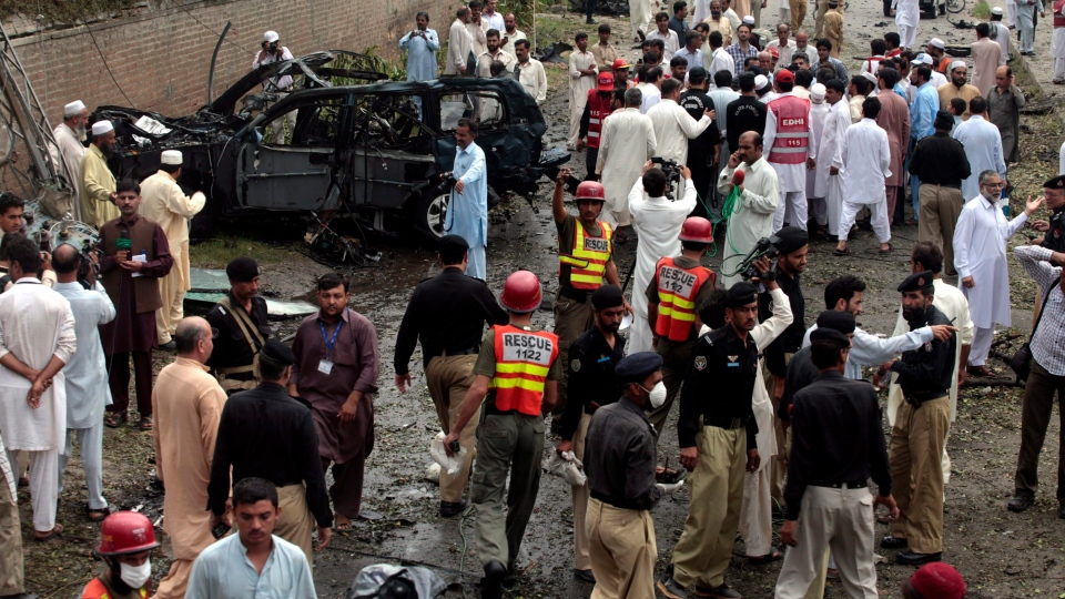 Officials and rescue volunteers gather at the bombing site in Peshawar, Pakistan on Monday, Sept. 3, 2012. (AP/Mohammad Sajjad)