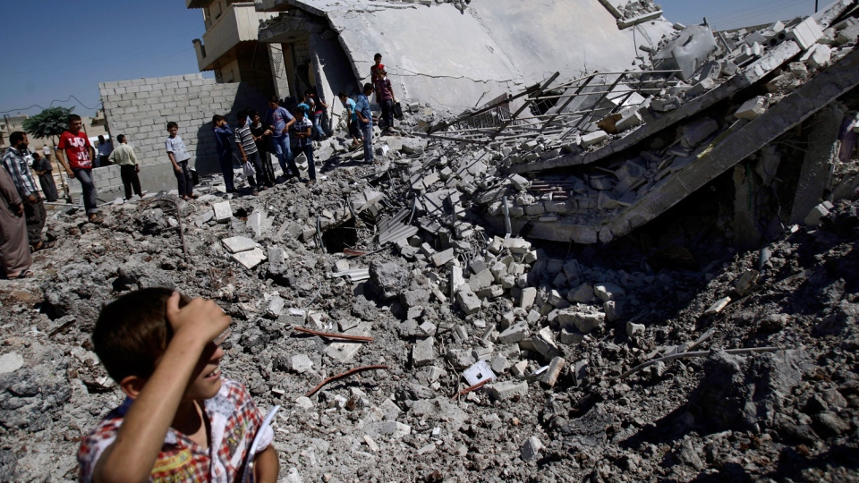 Syrians gather by the rubble of a house, destroyed from Syrian forces shelling early Monday, in the Syrian town of Azaz, on the outskirts of Aleppo, Monday, Sept. 3, 2012. (AP/Muhammed Muheisen)