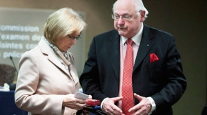 Sheila Fynes holds her son's medals as she speaks with lawyer Michel Drapeau before appearing at the Military Police Complaints Commission hearing into the suicide of her son, Cpt. Stuart Langridge, in Ottawa, Thursday, April 26, 2012. (Adrian Wyld / THE CANADIAN PRESS)