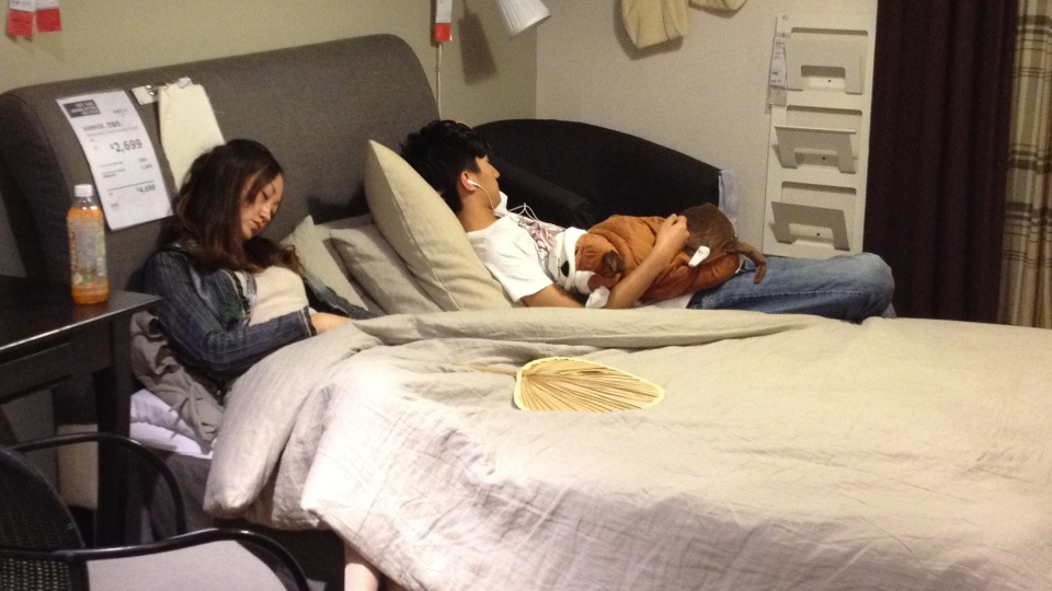 A couple sleeps on this showroom bed in a Beijing Ikea store. (Janis Mackey Frayer/CTV News)
