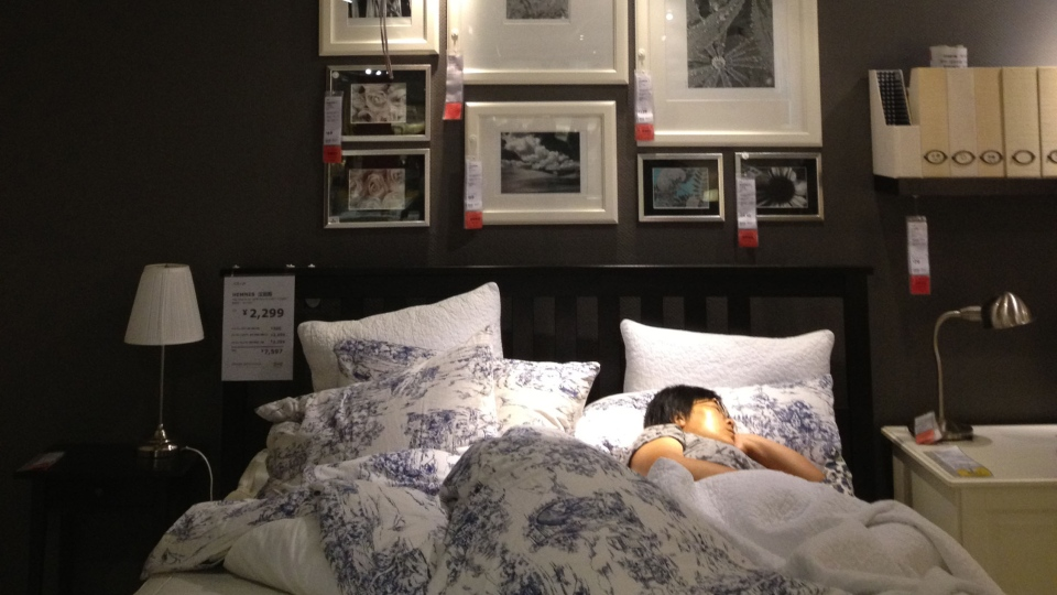 No assembly required: A woman dozes off under the covers of this bed in an Ikea showroom in Beijing. (Janis Mackey Frayer/CTV News)