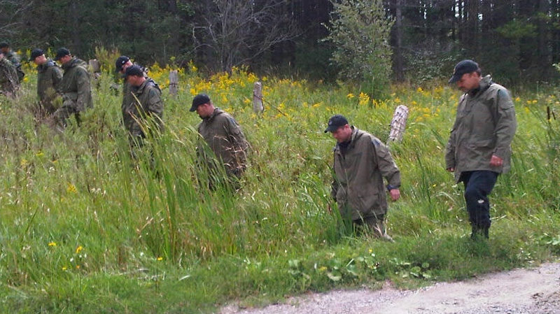 OPP officers are seen searching area near where human remains were found about 12 kilometres southeast Orangeville, Ont., on Sunday, Sept. 5, 2010. (Keith Hanley / CTV News)