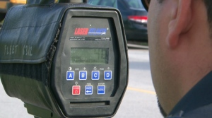 A Toronto police officer measures vehicles' speed in a school zone on Tuesday, Sept. 7, 2010.