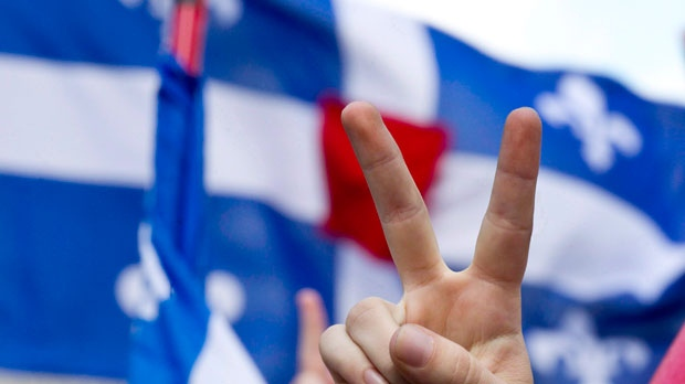 A demonstrator gives a peace sign in front of the Quebec flag on Friday, June 22, 2012. (The Canadian Press/Paul Chiasson)