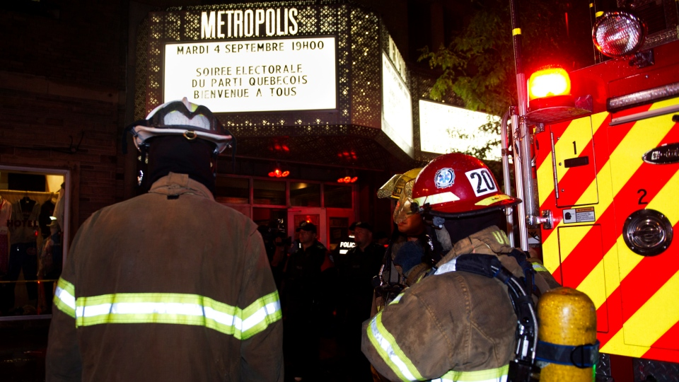 Police and fireman work at the rear of an auditorium where a gunman shot and killed at least one person during the PQ victory rally Wednesday, Sept. 5, 2012 in Montreal. (Paul Chiasson / THE CANADIAN PRESS)