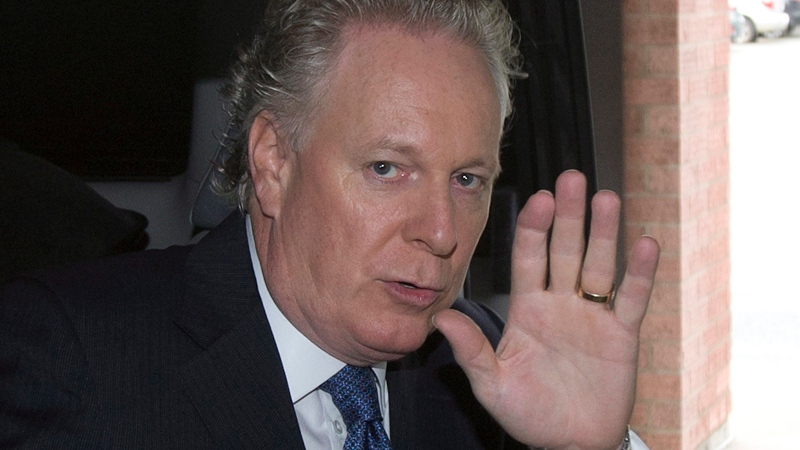 Quebec Liberal Party Leader Jean Charest waves as he leaves a hotel in Sherbrooke