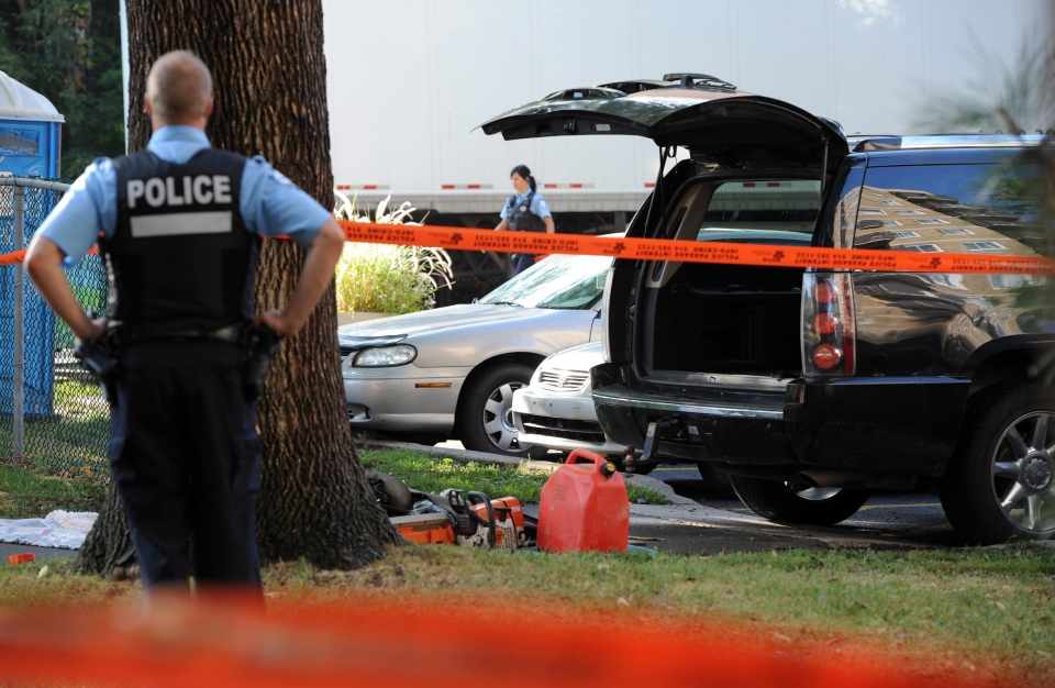 A police officer looks towards a black SUV that has had its contents removed at a crime scene outside the Metropolis in Montreal on Wednesday, Sept. 5, 2012. (Sean Kilpatrick /  THE CANADIAN PRESS)